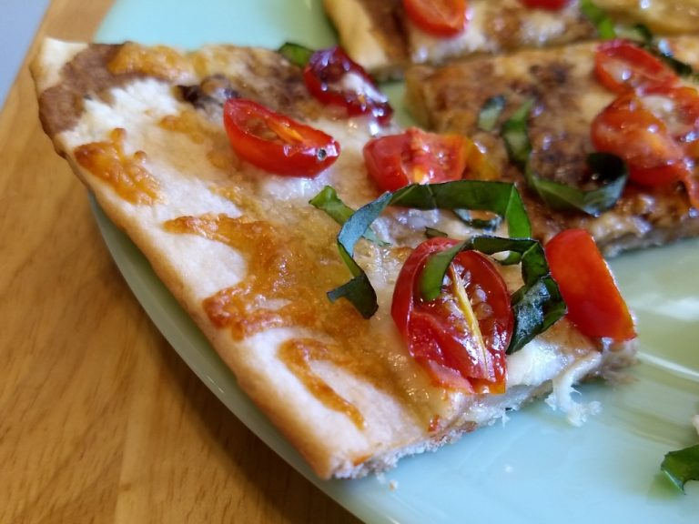 Fresh basil and tomato pizza with herbed crust and balsamic drizzle